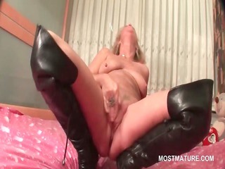 older in leather boots doing herself in ottoman